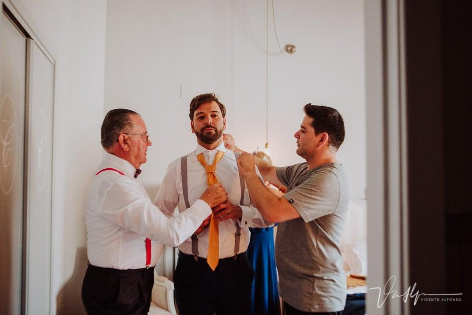 Padrino y hermano ajustando la corbata al novio