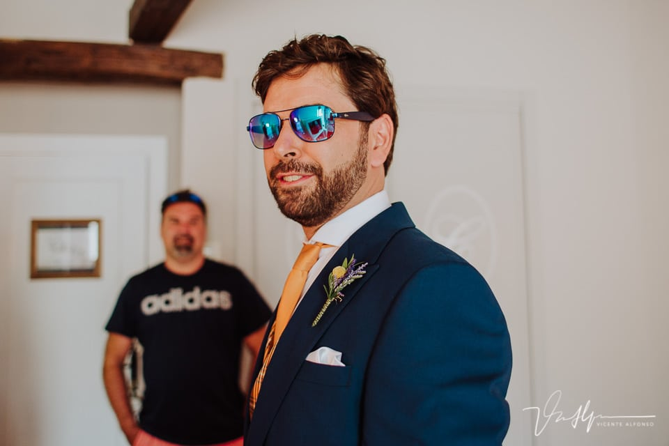 Novio con gafas de sol justo al terminar de vestirse