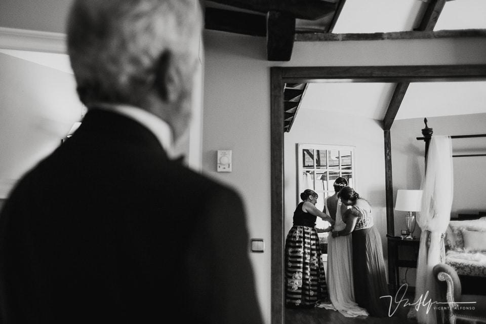 Padrino mirando como se viste su hija de novia