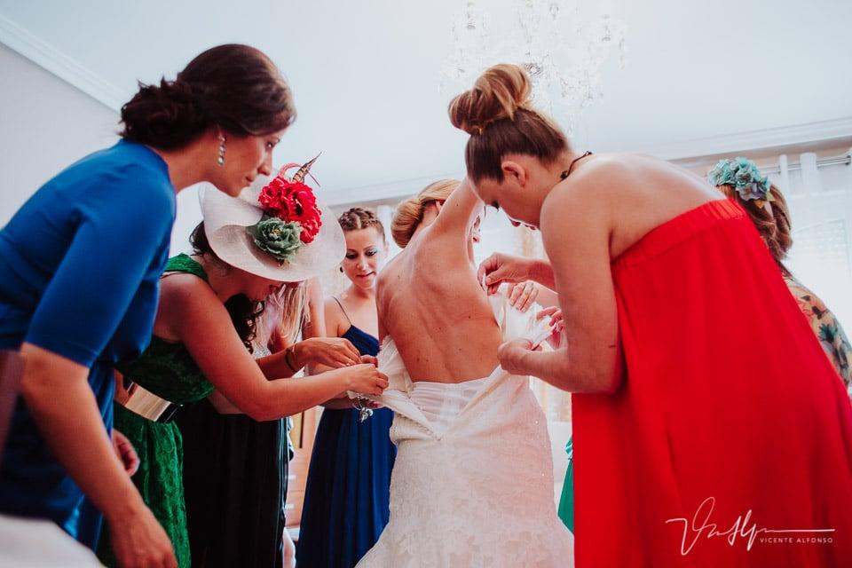 ajustando el traje de la novia con las amigas