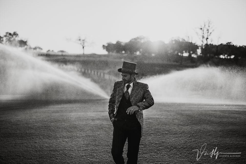 Novio con traje con chistera en campo de golf