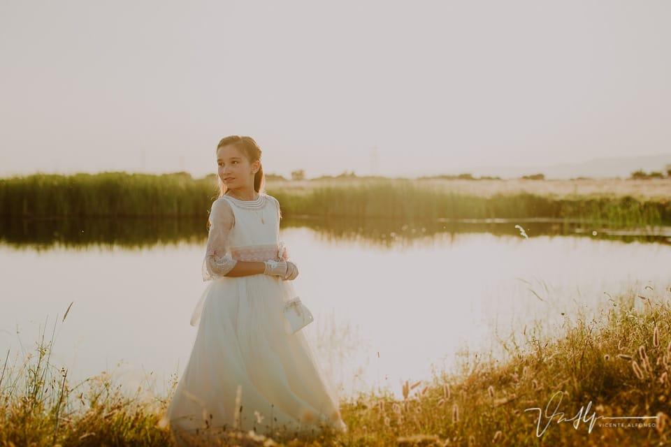 Niña vestida de comunión en exteriores junto a una laguna