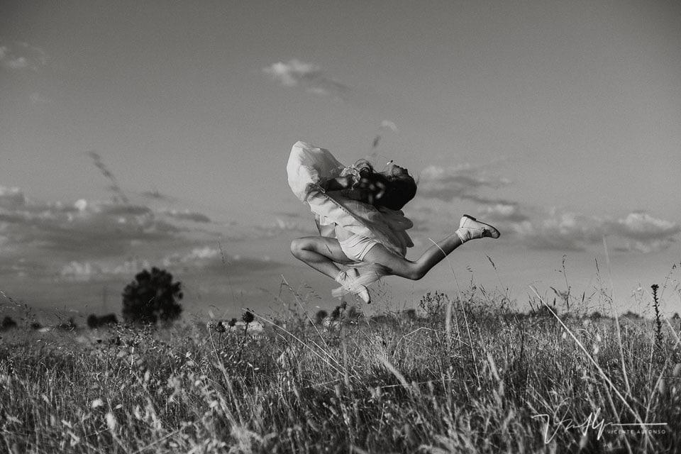 Niña vestida de comunión haciendo salto de gimnasia
