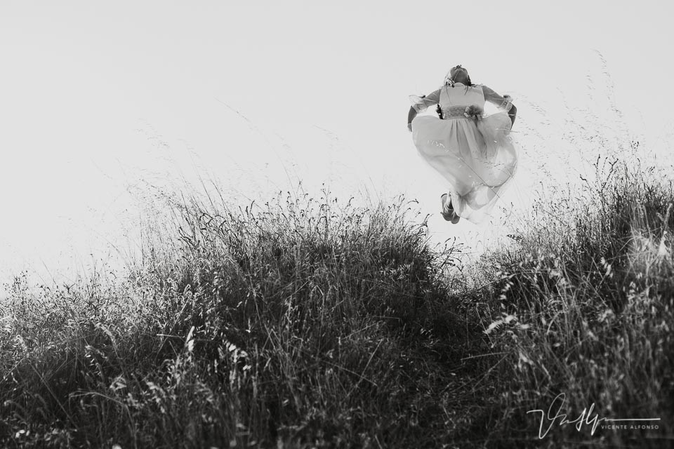 Niña vestida de comunión saltando
