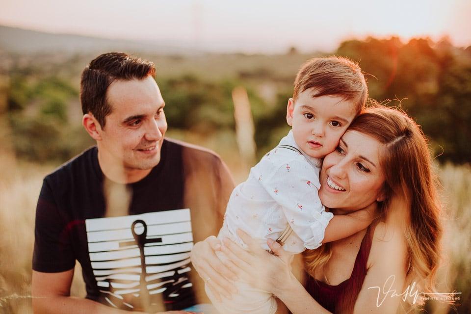 Plano cerrado familiar abrazando a su hijo al atardecer