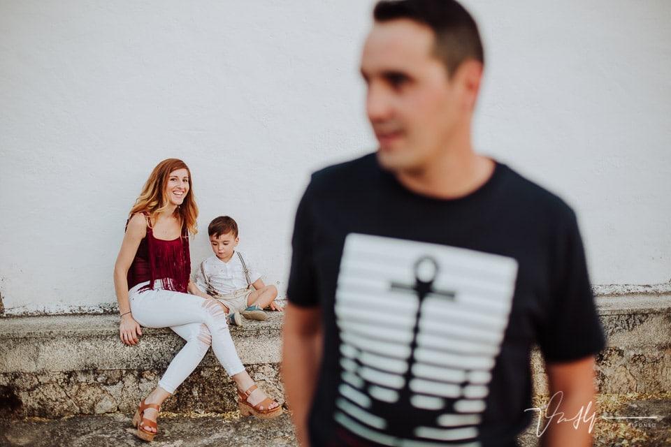 Madre jugando con su hijo y sonriendo mientras el padre camina