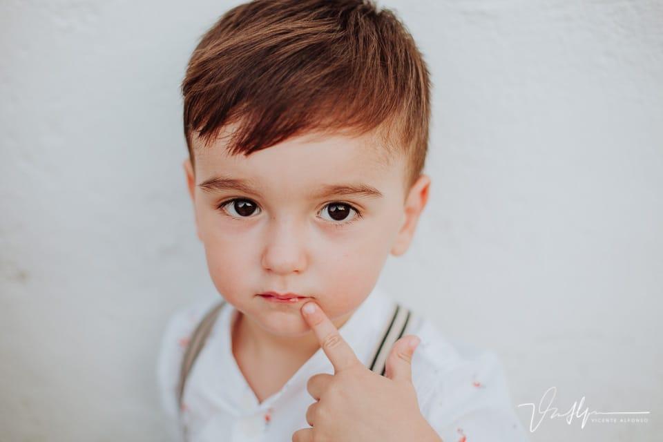 Retrato niño con el dedo en la boca