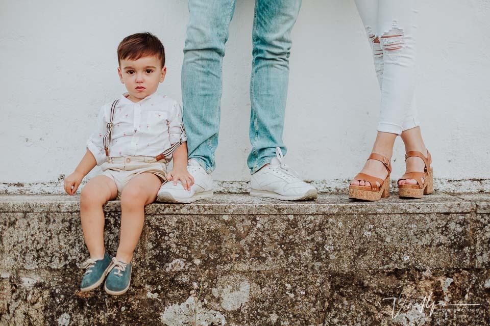 Niño de cuatro años entre los piés de sus padres