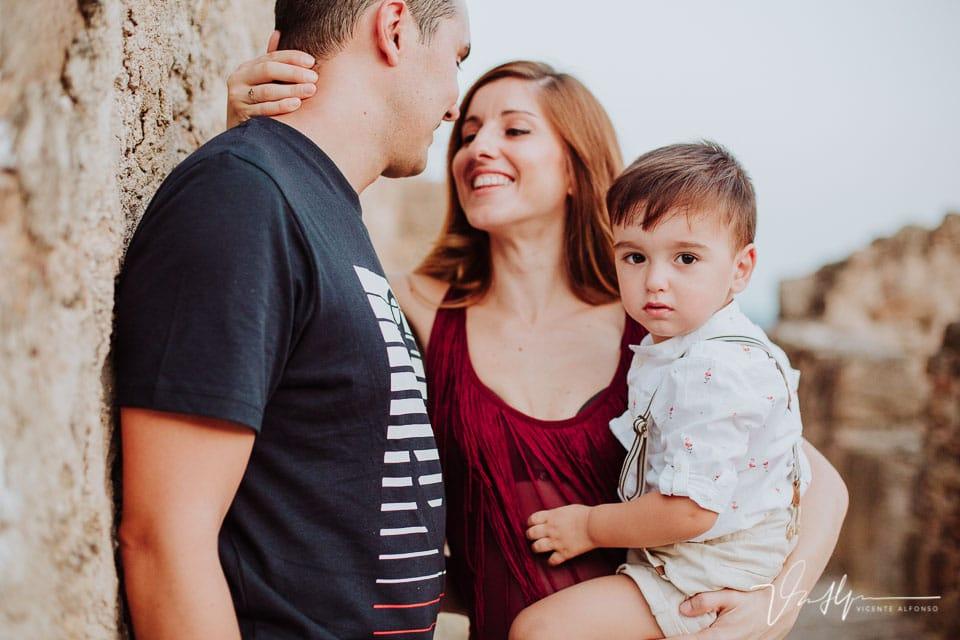 Reportaje familiar con su hijo en brazos mientras ellos se besan
