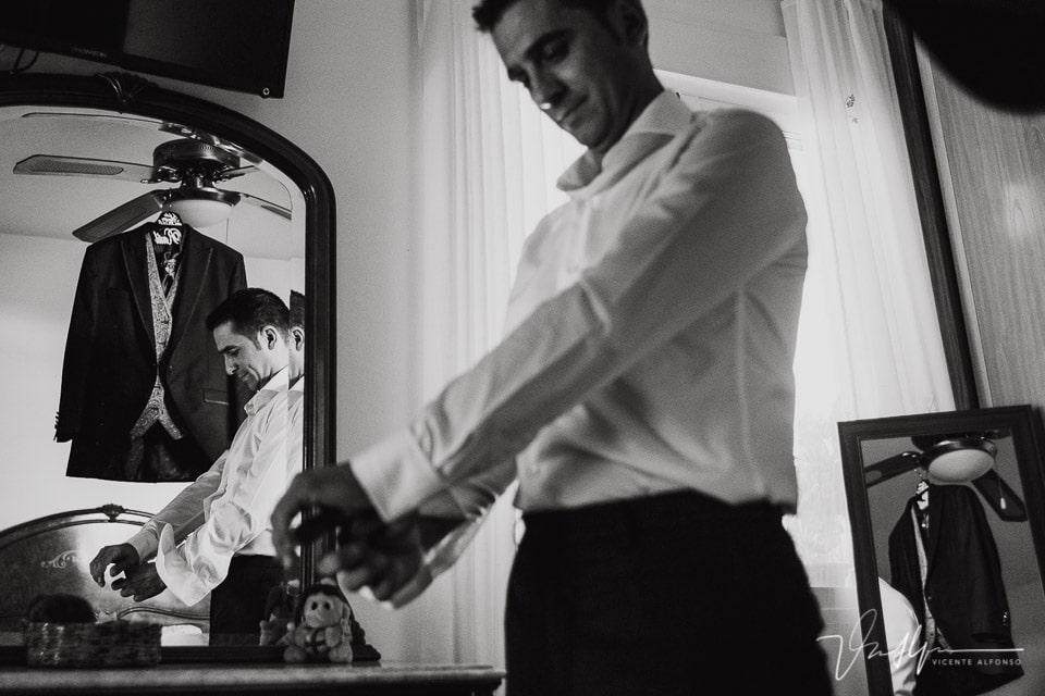 Novio poniéndose la camisa y los gemelos en su habitación