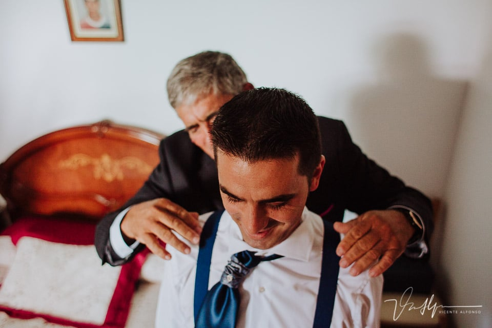 El padre del novio ajustándole los tirantes