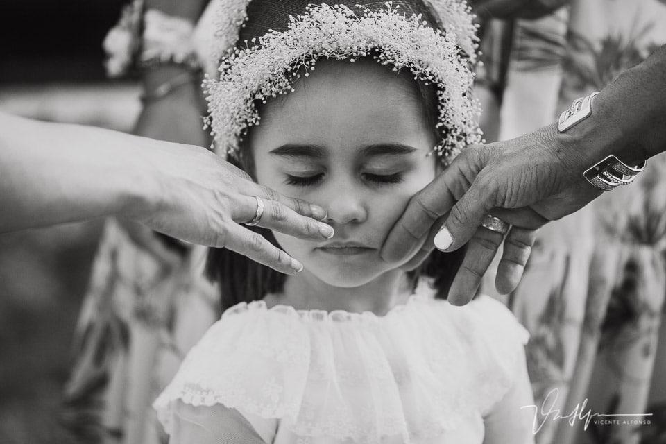 Retrato de niña mientras la acarician dos manos en una boda en Navalmoral