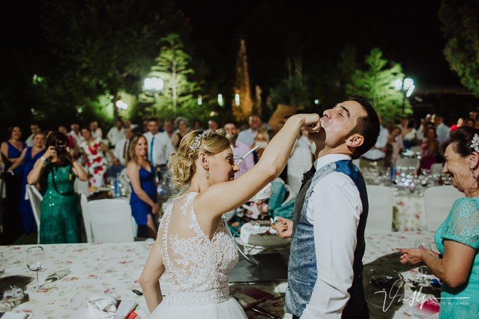 Novia dando tarta al novio con la mano