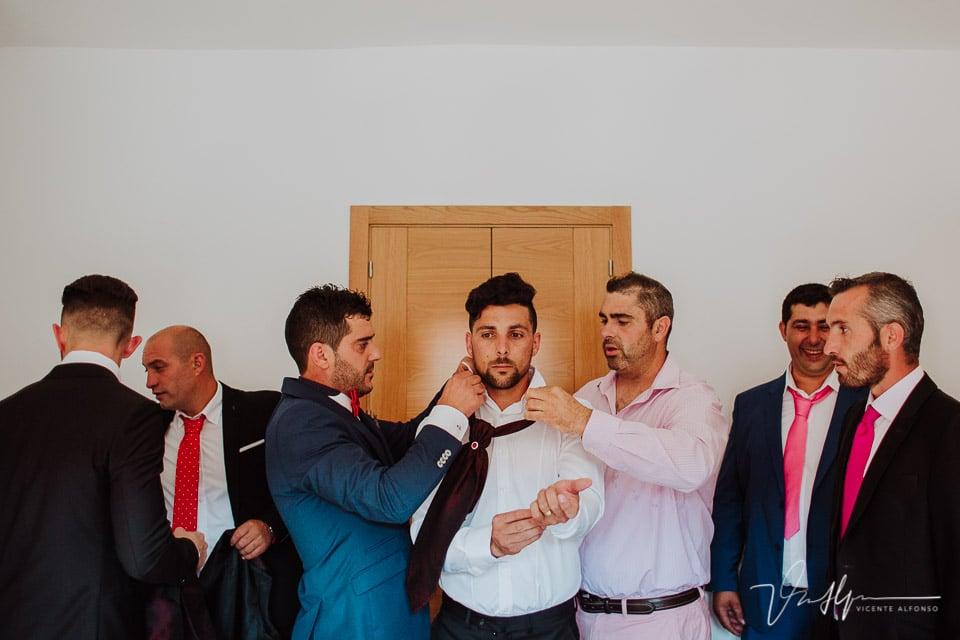 Amigos poniendo corbata al novio