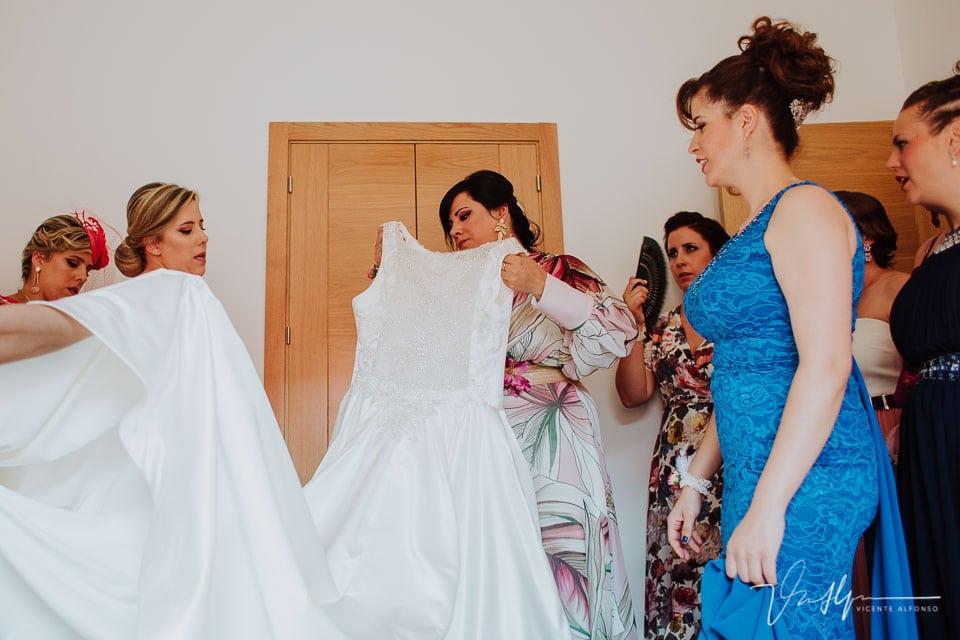 Amigas ayudando a vestir a la novia