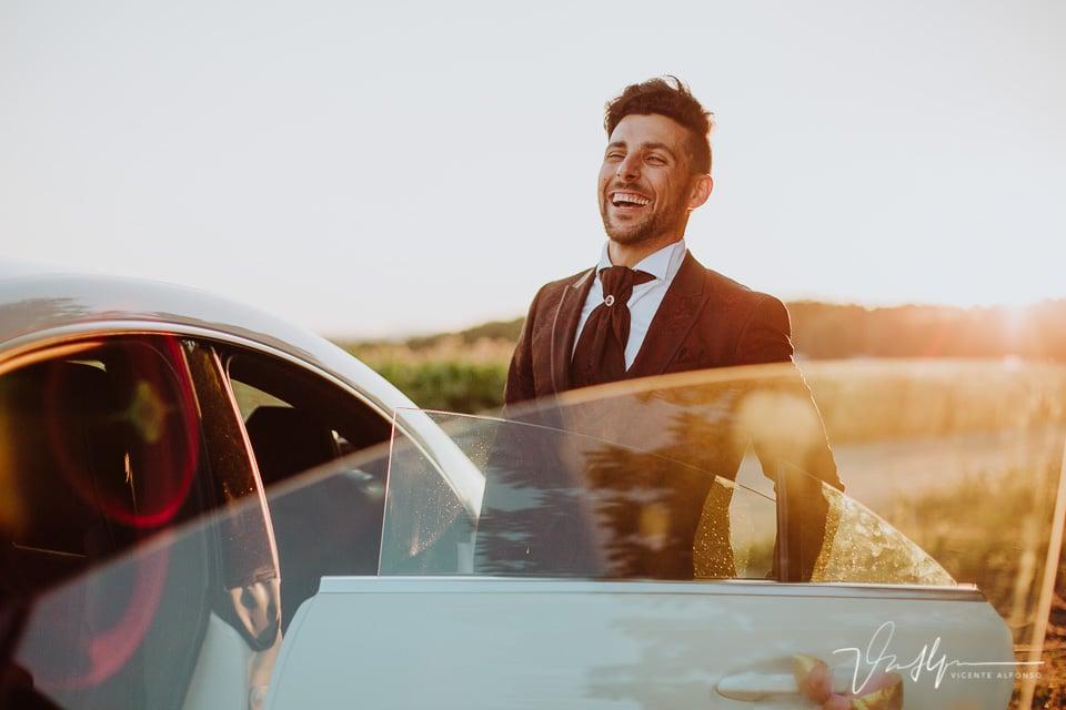 Novio riendo al atardecer entrando en el coche