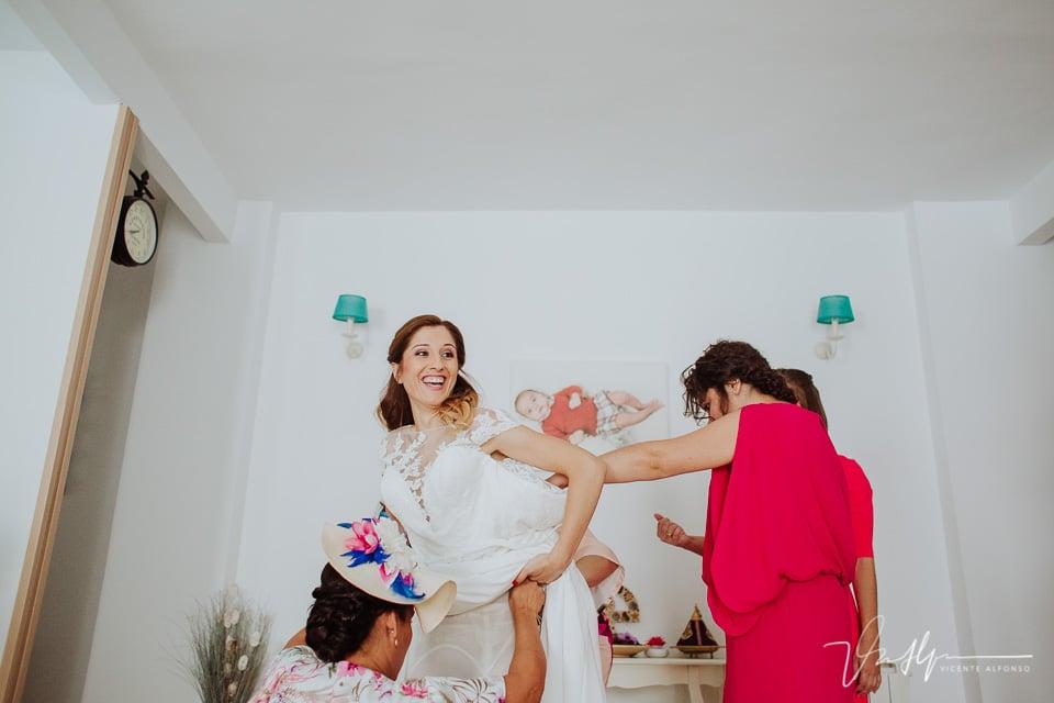 riendo mientras las amigas visten a la novia