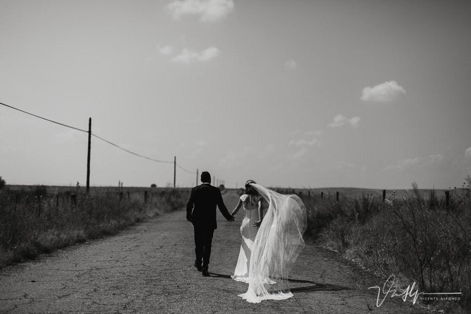 novios de espalda en la vía de servicio durante el reportaje de boda