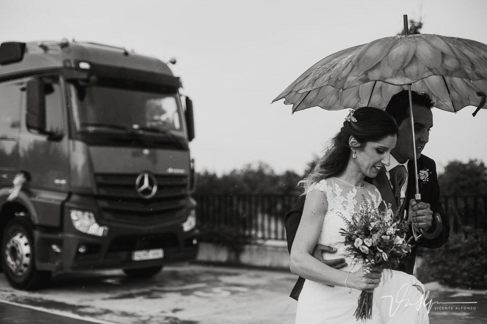 novios llegando al coctel entre la lluvia