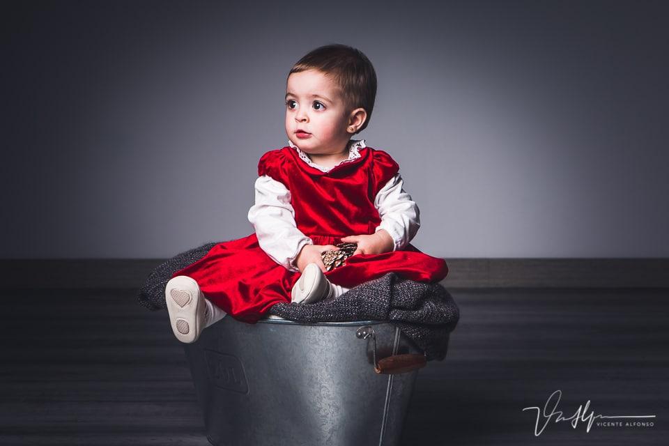 Bebé sentada en un cubo en un reportaje de estudio