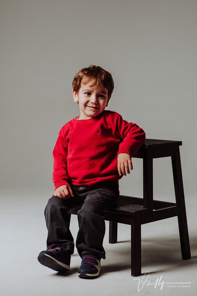 Niño pequeño sentado en escalera en estudio