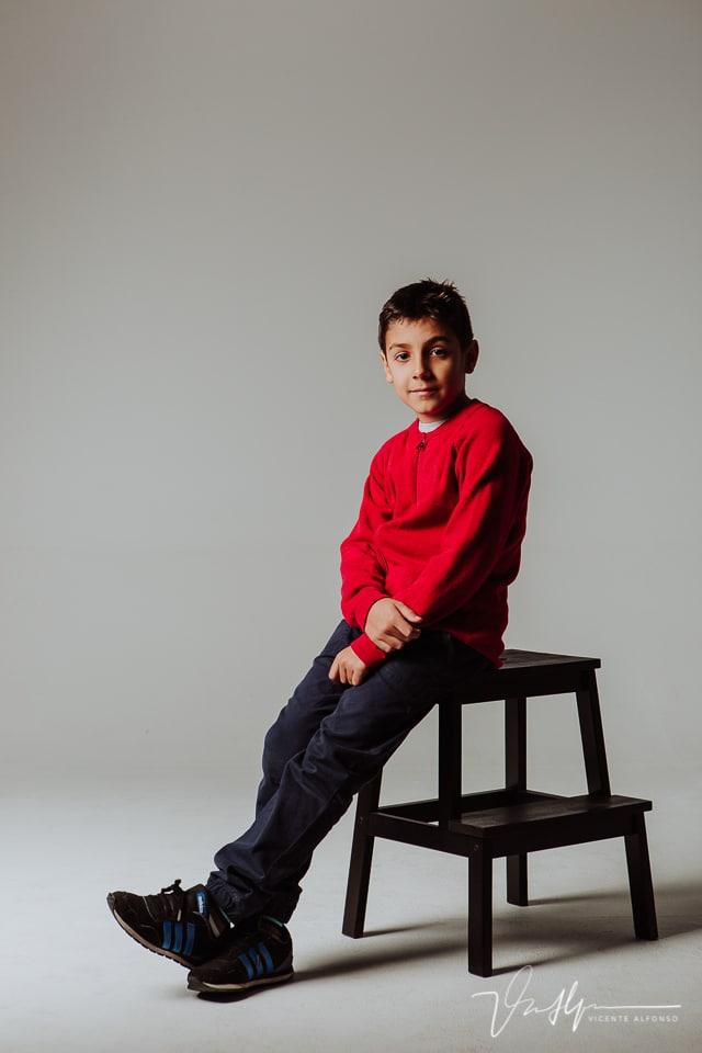 Niño adolescente sentado en escalera en estudio