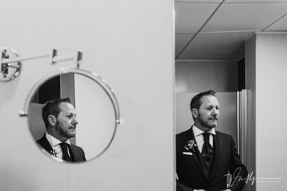 Reflejos en el espejo del baño mientras el novio se peina