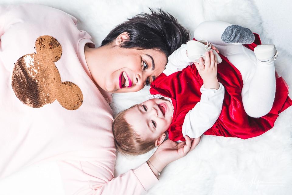Madre e hija riendo juntas sobre una alfombra