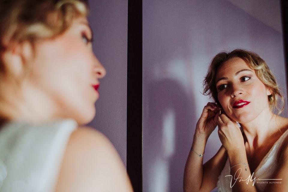 La novia colocándose los pendientes frente al espejo
