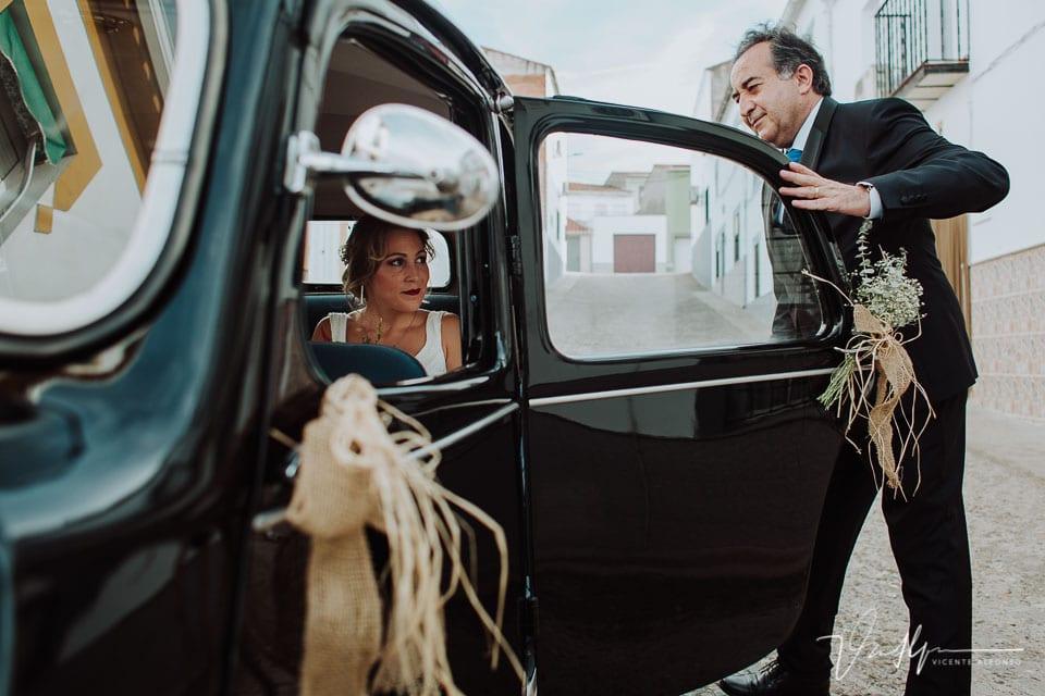 Padre cerrando la puerta al coche clásico para ir a la boda