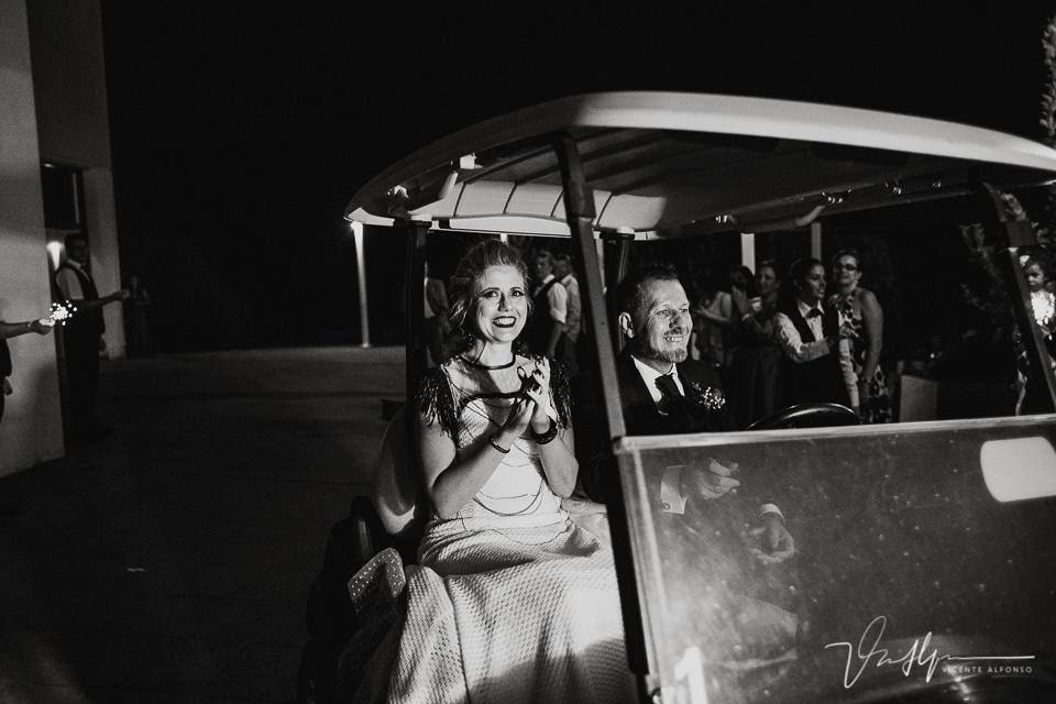 Los novios llegando al baile en un carrito de golf