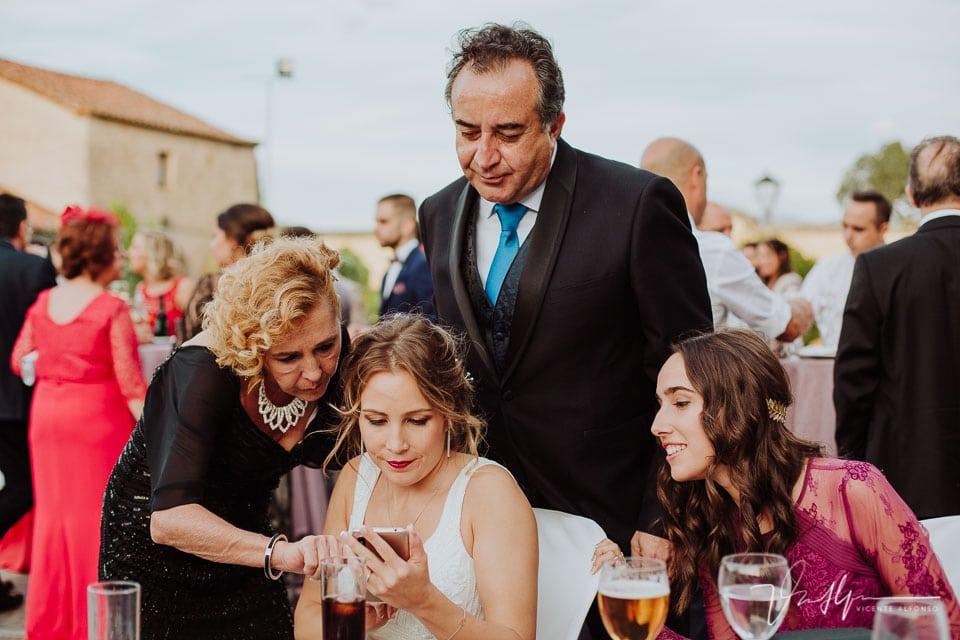 Familia de la novia mirando el móvil en el cóctel