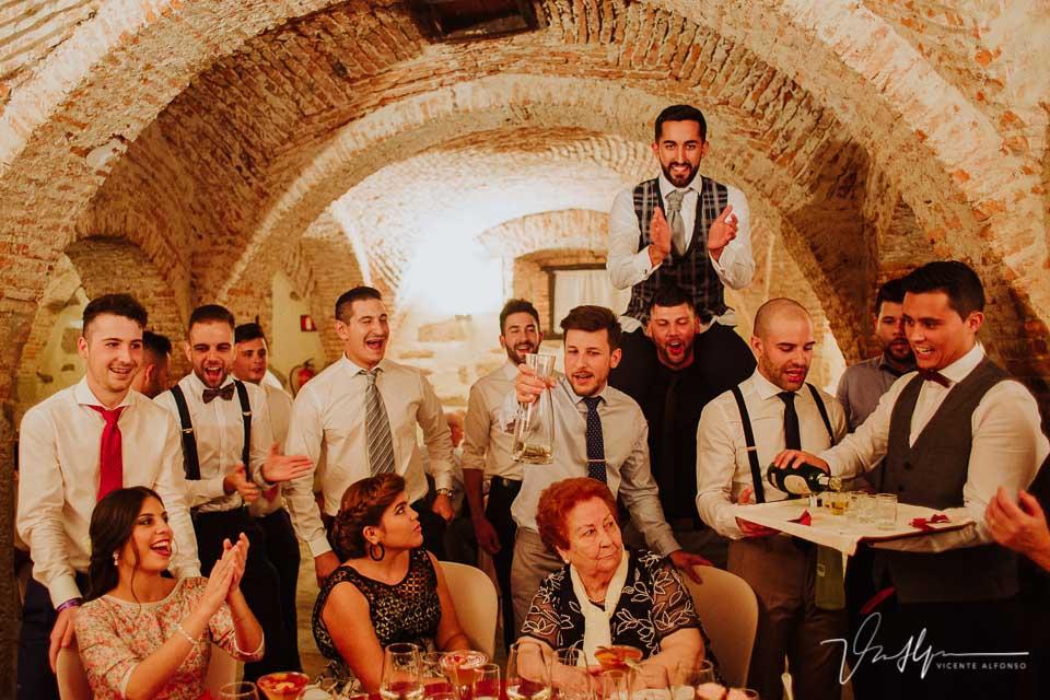 Novio y amigos pidiendo por las mesas en el banquete