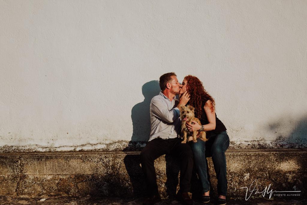 pareja besándose junto con su perrito