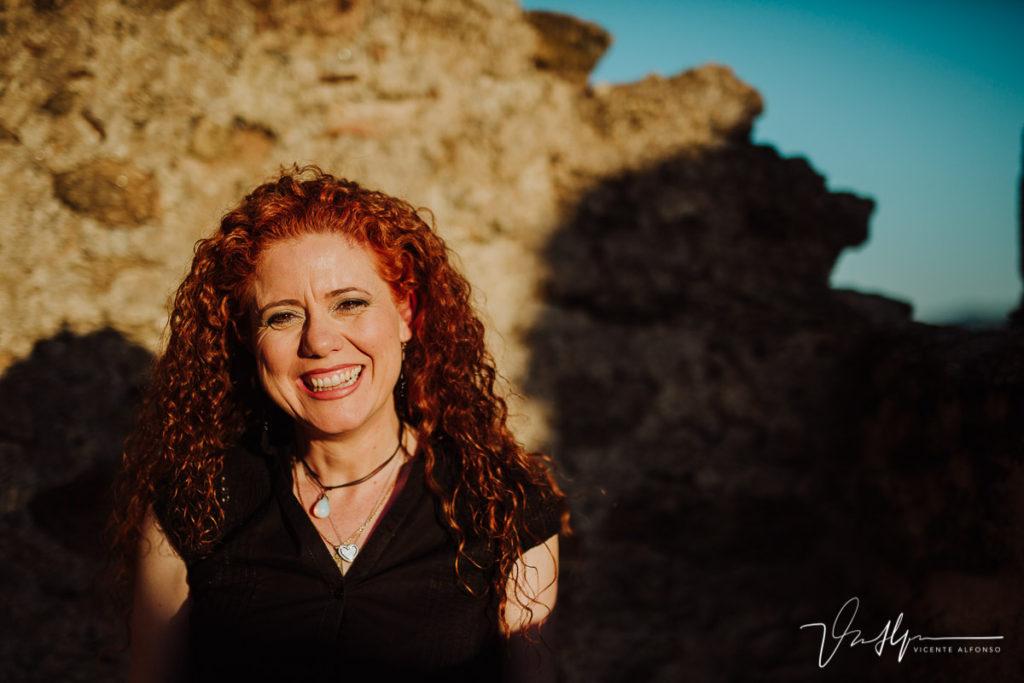Retrato mujer pelirroja con pelo rizado riendo