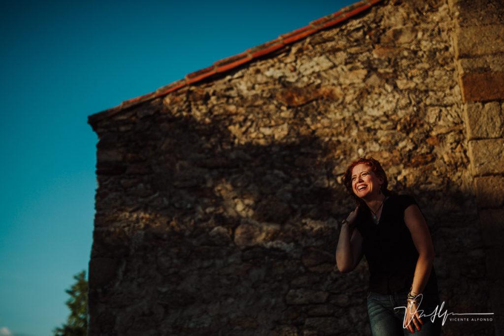 Mujer pelirroja con peli rizado riendo mientras la da la luz del sol en la cara