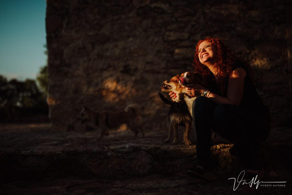 Mujer pelirroja riendo junto con sus perros