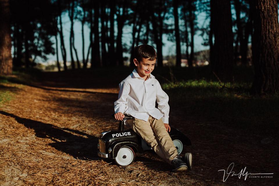 Niño posando junto a su coche de paseo