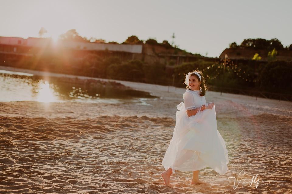 Niña andando y sujetando vestido al atardecer en la playa artificial del Hotel Vincci Valdecañas
