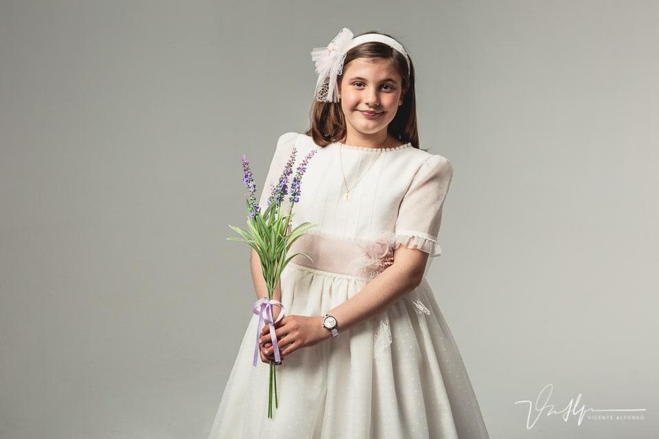 Niña vestida de comunión en estudio sujetando flores