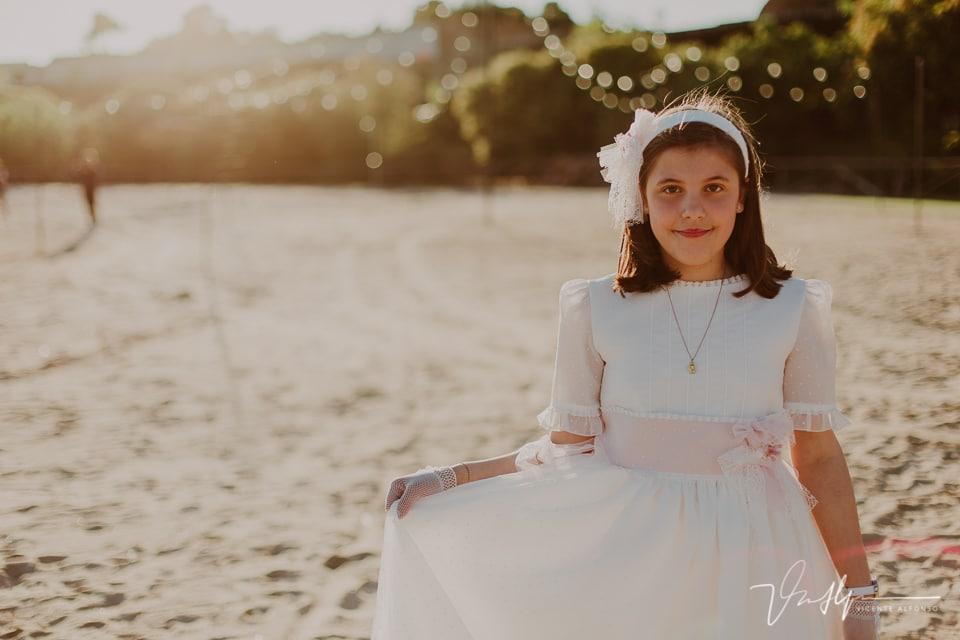 Niña sujetando falda del vestido de comunión en la playa artificial del Hotel Vincci Valdecañas