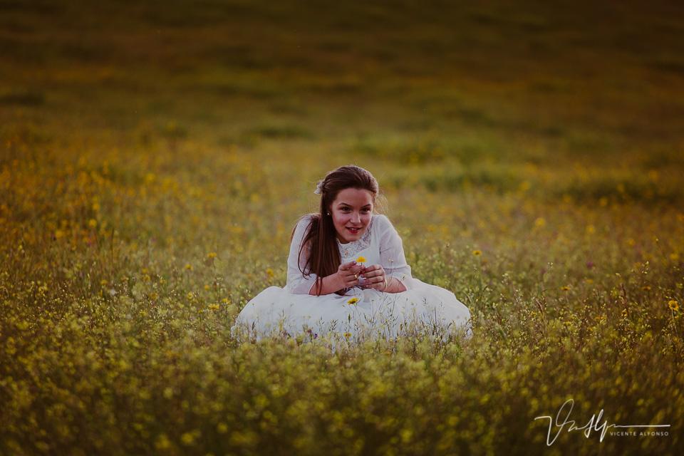 Niña de comunión sentada en el campo