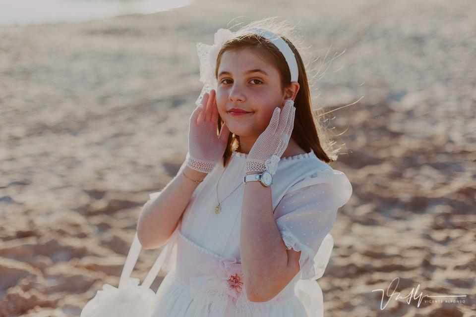 Niña vestida de comunión tocándose la cara con los guantes en la playa artificial del Hotel Vincci Valdecañas