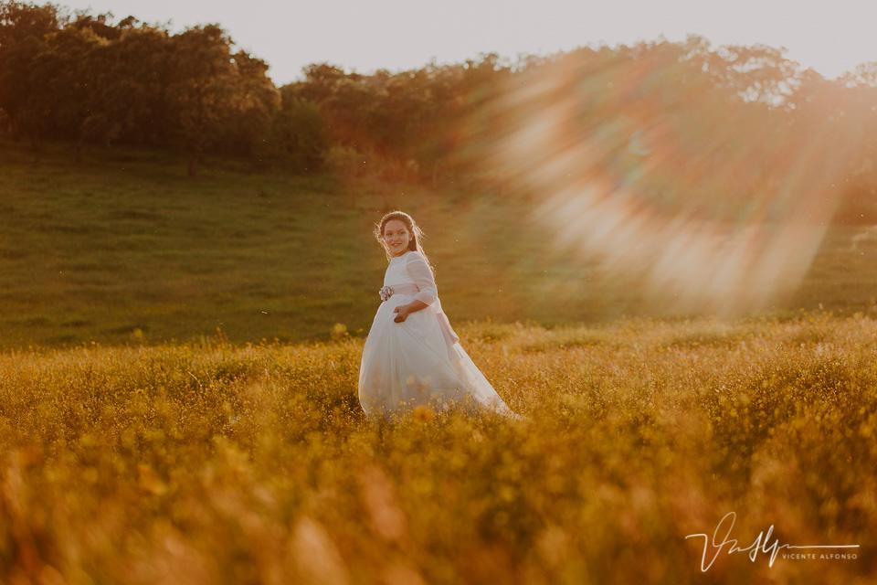 Niña vestida de comunión andando por el campo al atardecer