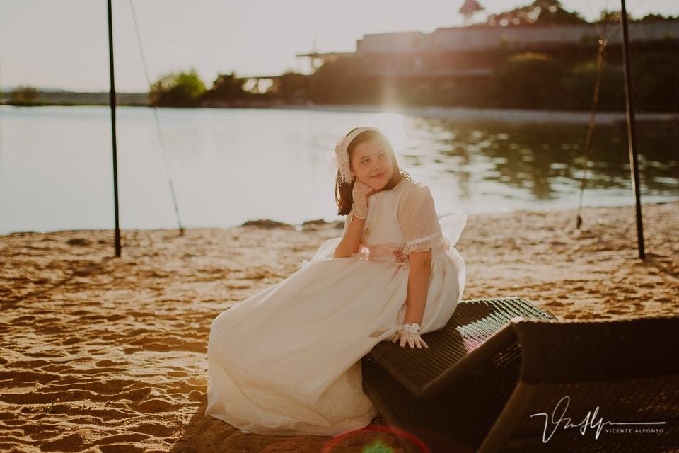 Niña de comunión sentada en una tumbona en la playa artificial del Hotel Vincci Valdecañas