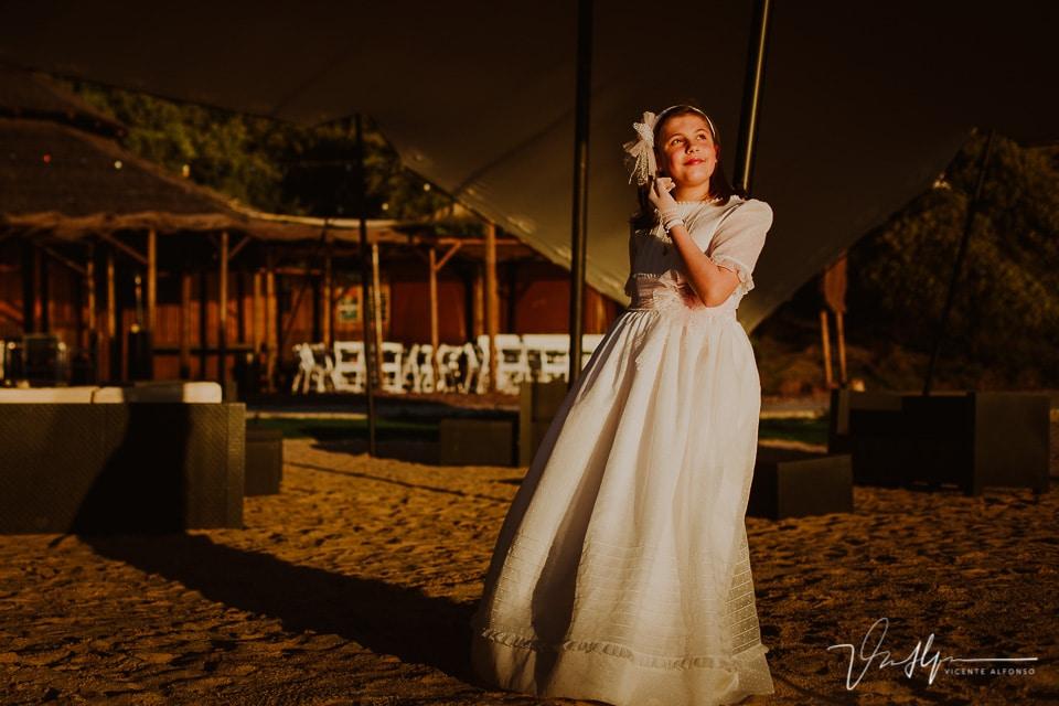 Niña apoyada vestida de comunión en la playa artificial del Hotel Vincci Valdecañas