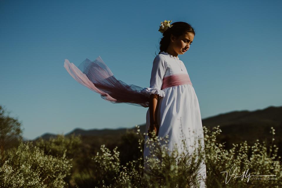 Niña vestida de comunión en el campo con el viento volando su vestido