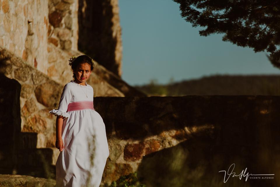 Niña vestida de comunión andando entre ruinas