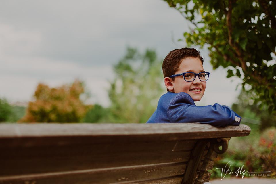 Retrato de niño de comunión sentado en un banco