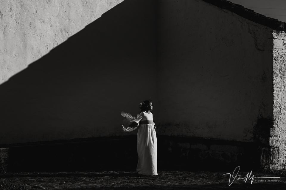 Niña de comunión en blanco y negro entre luz y sombra